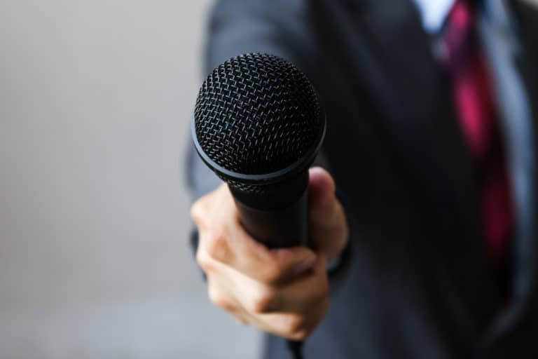 man-business-suit-holding-microphone-indicating-business-formal-events-scaled